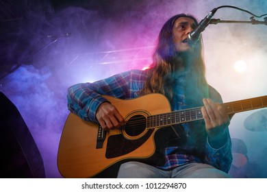 The vocalist plays the acoustic guitar. Stage light, smoke.