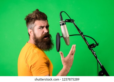 Vocalist singing in condenser microphone. Bearded man singing with microphone. Concert and music concept. Brutal bearded singer with microphone on stage. Male lead vocalist singing in recording studio