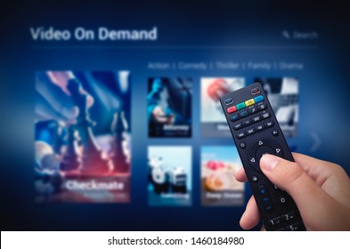 VOD service screen with remote control in hand. Video On Demand television internet stream multimedia concept