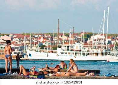 Vodice, Croatia -  August 21, 2016: People in swimsuits sunbathing on the pier in Adriatic coast and sailboats , ship and houses in the distance behind them