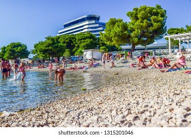 Vodice, Croatia - July 7, 2018: Vacationers on the beautiful pebble beach.