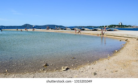 Vodice, Croatia - July 8, 2018: Vacationers on the beautiful pebble beach.