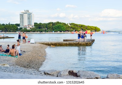 Vodice, Croatia - July 9, 2018: Vacationers on the beautiful pebble beach.