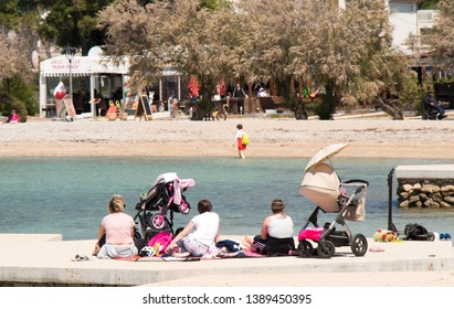 Vodice, Croatia - May2, 2019: Group of mothers sitting on the beach in spring off-season with baby strollers next to them