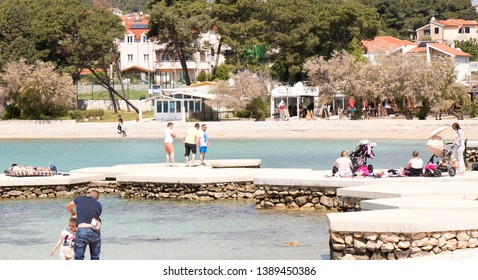 Vodice, Croatia - May2, 2019: People sitting and walking on the beach in spring off-season