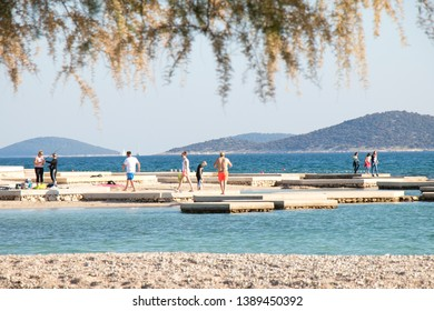 Vodice, Croatia - May2, 2019: People walking on the beach in spring off-season