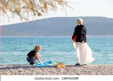 Vodice, Croatia - May2, 2019: Woman and a girl standing at the beach in spring off-season, from behind