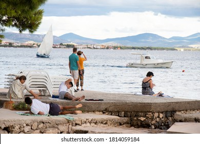 Vodice, Croatia - September 1, 2020: People relaxing on the beach in off season and boats in the sea