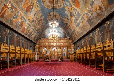 Vodita Monastery, Romania - June15,2019: The empty interior of a small orthodox church. Wooden pew, red carpet, icons, mural paintings with saints and the altar.