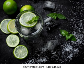 Vodka cocktail, lemon juice, syrup and mint leaf salt in clear glass. On a black background.