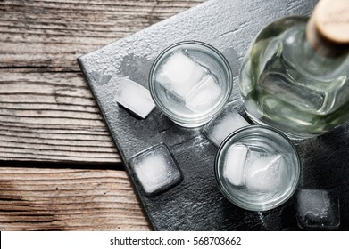 Vodka gin in shot glasses on rustic wood background top view