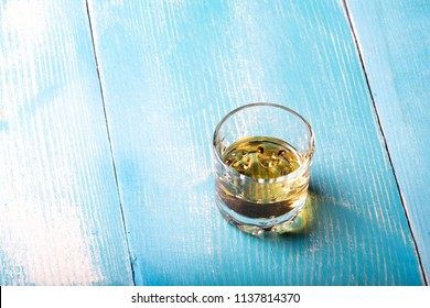 vodka in a glass on the table, one glass on a wooden table in blue