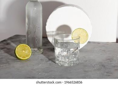 Wodka mit Eis und Kalk in Glas und Flasche Wodka. Schatten und Trends des Sonnenlichts