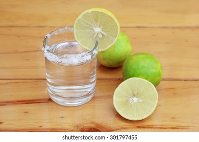 Vodka with lemon on wooden background