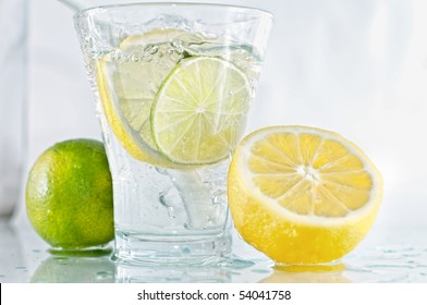 Vodka, lime and lemon in glass with ice