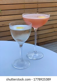 A vodka martini and a cosmopolitan are on top of a white table with a wooden planter in the background.