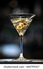 Vodka martini on a bar with three olives