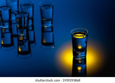 Vodka on a black reflective background. Strong alcoholic drink in color bright lights.
