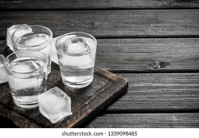 Vodka on the ice on the cutting Board. On black wooden background