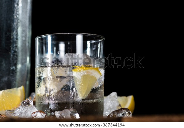 Vodka on the rocks (on an old wooden table) as detailed close-up shot