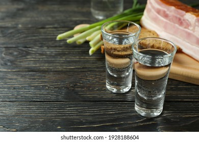 Vodka, onion, bacon and bread on wooden background