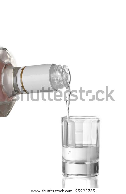 Vodka poured into a glass isolated on white