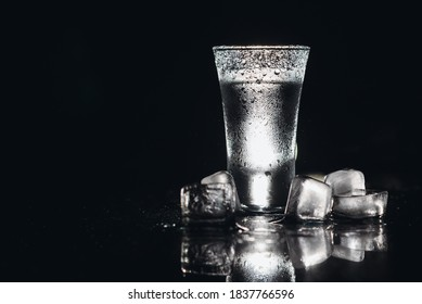 Vodka in shot glasses on black background, iced strong drink in misted glass