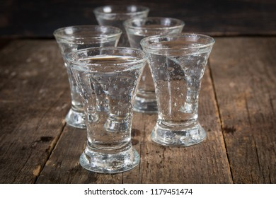 vodka in shot glasses on a dark wooden background