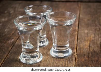vodka in shot glasses on a dark wooden background