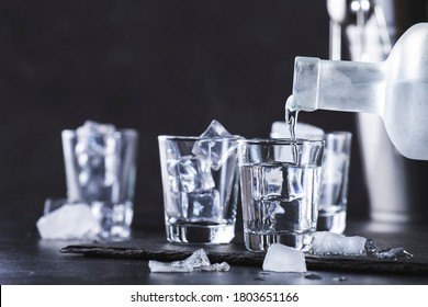 Vodka in shot glasses pouring out of the bottle on black stone background, iced strong drink in misted glass
