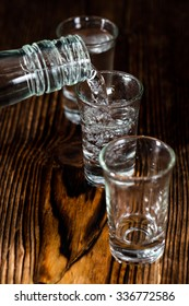 Vodka Shot with ice on an old rustic wooden table
