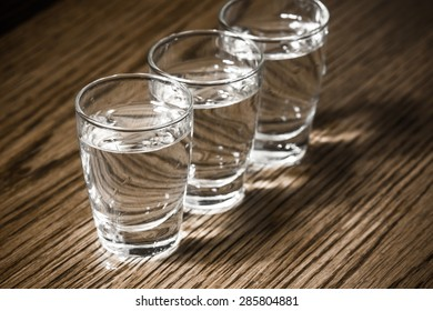 Vodka shots filled with alcohol on wooden bar.