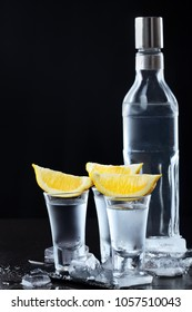 Vodka. Shots, glasses and bottle with vodka and lemon with ice .Dark stone background.Copy space .Selective focus