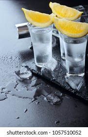 Vodka. Shots, glasses with vodka and lemon with ice .Dark stone background.Copy space .Selective focus