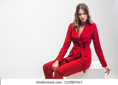 vogue model seting on white cupe in red elegant suit