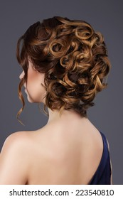 Vogue. Rear View of Woman's Festive Hairstyle. Waved Hairs