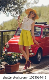 Vogue style elegant portrait of beautiful fashion woman wavy shine blonde long hair. Model in summer hat yellow skirt red shoes with bright makeup beside red retro car at Amalfi coast in Italy