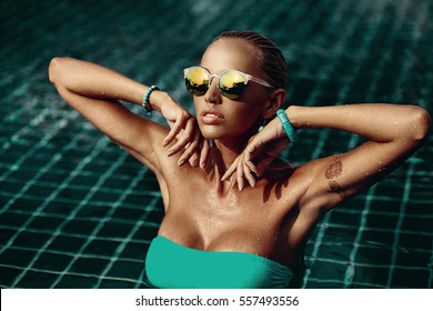 Vogue style fashion portrait of beautiful chic woman in water - close up