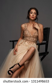 Vogue style fashion portrait of young elagent woman in evening dress sitting on high chair with crossed legs. Pretty lady portrait with soft light