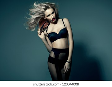 Vogue style photo of attractive blonde woman in studio