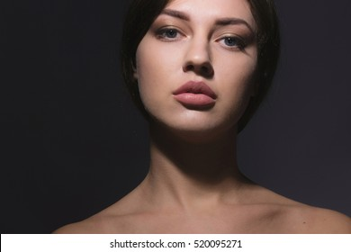 vogue style portrait of beautiful delicate woman with sensual lips and naked showlder on dark background