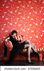 Vogue style vintage portrait. Retro-stylized woman sitting on red sofa.