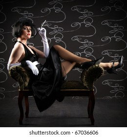 Vogue style vintage portrait. Retro-stylized smoking woman with mouthpiece sitting on black sofa.
