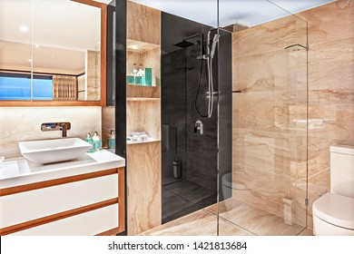A voguish bathroom featuring a glass-separated shower area, a vanity basin, and a toilet seat