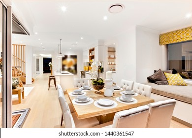 Voguish dining area attached to the kitchen with a snack counter and a stylish seating area by the bay window next to the dining table