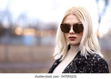 voguish young blond woman in leopard coat with sunglasses walking on the street in sunset