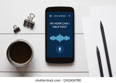 Voice assistant concept on smart phone screen with office objects on white wooden table. All screen content is designed by me. Flat lay