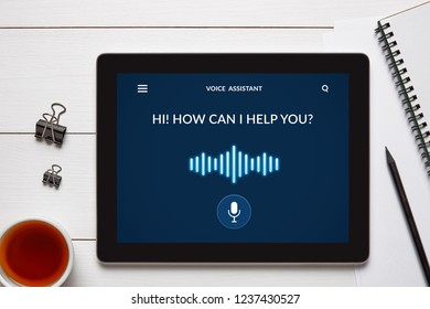 Voice assistant concept on tablet screen with office objects on white wooden table. All screen content is designed by me. Flat lay