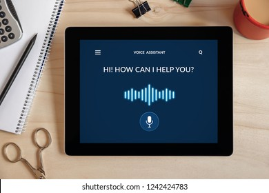 Voice assistant concept on tablet screen with office objects on wooden desk. All screen content is designed by me. Top view