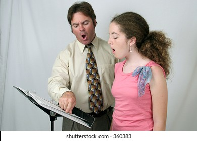A voice coach and student singing together.